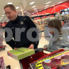 Wendy Kemp - For The Daily Chronicle<br /> Aallyah Day, 7, and her helper, Officer Tony Densberger, price check their toy selection during the Shop with a Cop event at Target on Sunday.<br /> DeKalb 12/11/11