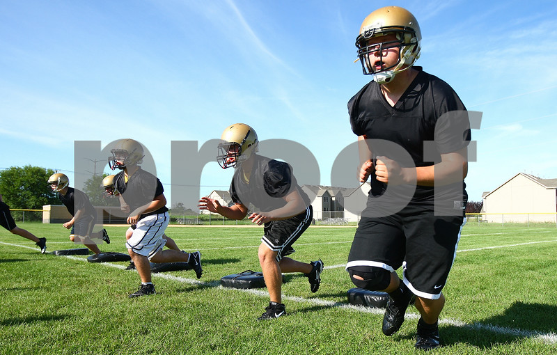 Kyle Bursaw – kbursaw@daily-chronicle.com<br /> <br /> Evan Short (far right) and other varsity players run a drill during the first day of football practice Wednesday morning at Sycamore High School.<br /> <br /> Wednesday, Aug. 10, 2011.