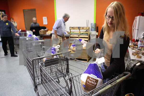 Kyle Bursaw – kbursaw@shawmedia.com<br /> <br /> Angie Boesche, 20, places a turkey into a shopping cart as she and other volunteers at the Salvation Army in DeKalb assemble meal packages to be distributed to local families on Tuesday, Nov. 22, 2011.