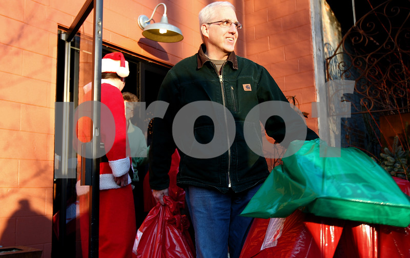 Kyle Bursaw – kbursaw@shawmedia.com<br /> <br /> Tom Warzecha brings multiple bags of gifts out of Blumen Gardens in Sycamore, Ill. to his vehicle. Warzecha and other Goodfellows of DeKalb-Sycamore volunteers delivered gifts to families on Saturday, Dec. 24, 2011.