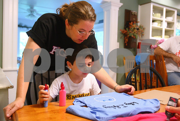 Kyle Bursaw – kbursaw@daily-chronicle.com<br /> <br /> Julianna Ladas helps her son Kaden, 6, make a shirt to wear during the upcoming Relay for Life. The entire family made shirts at their Sycamore home on Saturday, May 21, 2011.