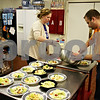 ANDREW MITCHELL — amitchell@shawmedia.com<br /> Christine Robinson (left) and James Wolfe fill salad bowls during Feed'em Soup's Thanksgiving meal Wednesday. Organizers predicted around 200 people would come for the free turkey dinner.