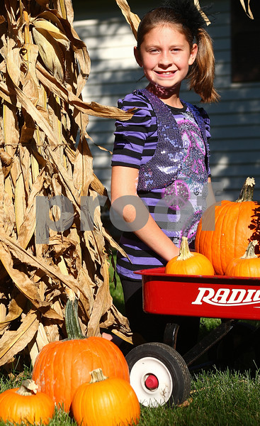 "Kyle Bursaw – kbursaw@shawmedia.com<br /> <br /> Hanna Diehl, 10, pictured here with the decorations in front of her Sycamore home, won the Pumpkin Festival theme contest with her submission ""50 Fabulous Years of Pumpkins.""<br /> <br /> Monday, Oct. 3, 2011."