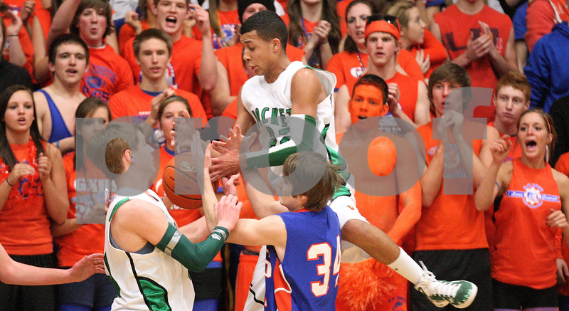 Kyle Bursaw – kbursaw@daily-chronicle.com<br /> <br /> Genoa-Kingston's Adam Price battles for a rebound with Rock Fall's Steven Armoska (left) and Davontay Euell (center) during the first quarter.<br /> The Genoa-Kingston Cogs defeated the Rock Falls Rockets 62-49 in Genoa, Ill. on Tuesday, March 1, 2011.