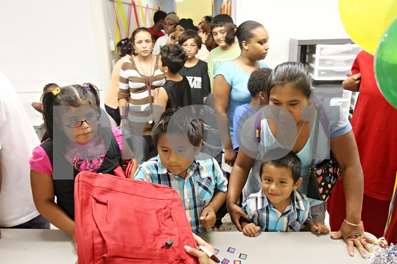 Rob Winner – rwinner@daily-chronicle.com<br /> <br /> (From left to right) Leslie Munoz, 9, Kevin Munoz, 6, and Jesse Munoz, 4, accompanied by their mother Saturnina Bernadino, each receive a free back pack while attending the Back to School Fair at Conexion Comunidad on Thursday night in DeKalb.
