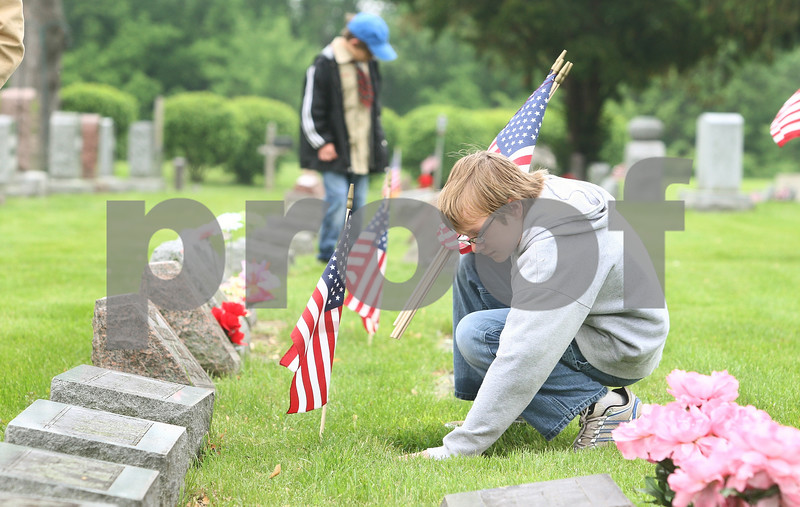 Kyle Bursaw – kbursaw@daily-chronicle.com<br /> <br /> Christopher Allen (right) double-checks the graves at Fairview Park Cemetery to make sure each veteran has an American flag. Multiple scout troops pitched in the effort on Saturday, May 28, 2011.