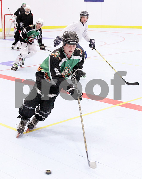 Kyle Bursaw – kbursaw@daily-chronicle.com<br /> <br /> Josiah Wells cruises with the puck as fellow Chi-Town Shamrocks teammate Sean Conlon (back left, in green jersey) follows the action at the Kishwaukee YMCA during the open skate on Thursday, Jan. 6, 2011.