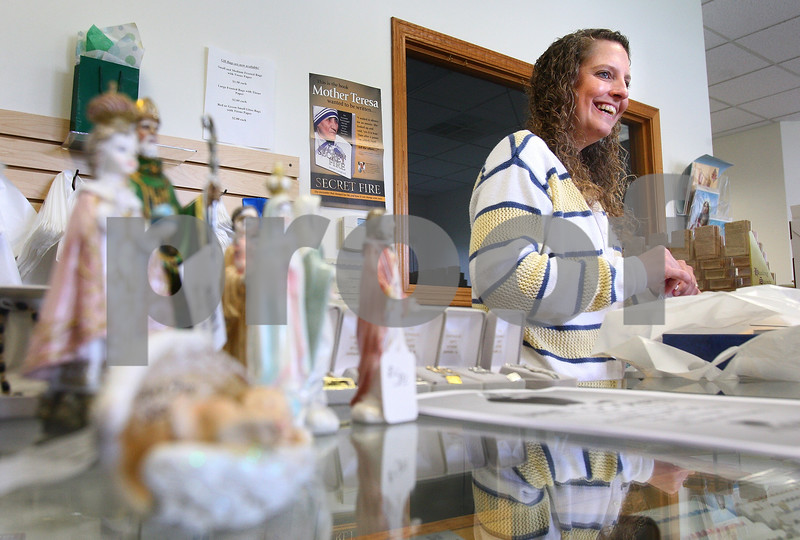 Kyle Bursaw – kbursaw@daily-chronicle.com<br /> <br /> Colleen Solorio, the manager of The Catholic Gift Store, bags up a customer's purchases on Wednesday, June 8, 2011.