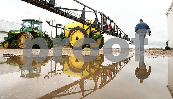 Kyle Bursaw – kbursaw@daily-chronicle.com<br /> <br /> Mike Schweitzer walks towards his sprayer, which he was doing maintenance on at his farm in Esmond, Ill. on Wednesday, April 27, 2011 because it was too wet and cold to start planting.