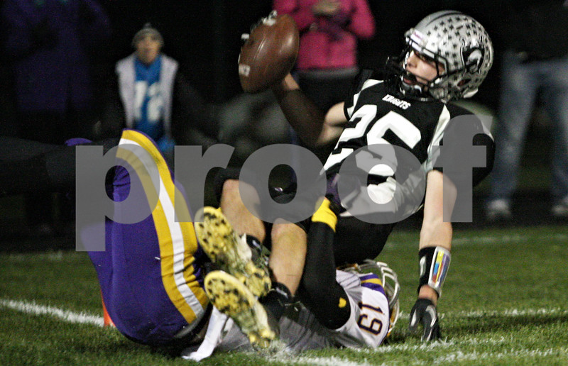 Rob Winner – rwinner@shawmedia.com<br /> <br /> Kaneland's Sean Carter (25) is tackled by Belvidere's Marcus Gooden (19) near the goal line after a reception during the second quarter in Maple Park on Friday, Oct. 28, 2011.