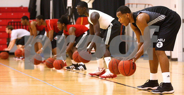 Kyle Bursaw – kbursaw@daily-chronicle.com<br /> <br /> DeAndre Barnette (right) and several other NIU basketball players go through some dribbling drills on Victor E. Court at the Convocation Center on Tuesday, July 26, 2011