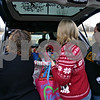 Jeff Engelhardt – jengelhardt@shawmedia.com<br /> Sue Zarlenga (left), Julie Barbosa (middle) and Abby Elliot (right) unload a trunk full of Christmas gifts at the Department for Children and Family Services in DeKalb Tuesday for foster children in the area. Elliot raised $500 in less than a day to make sure children in the Department of Children and Family Services system would receive gifts.