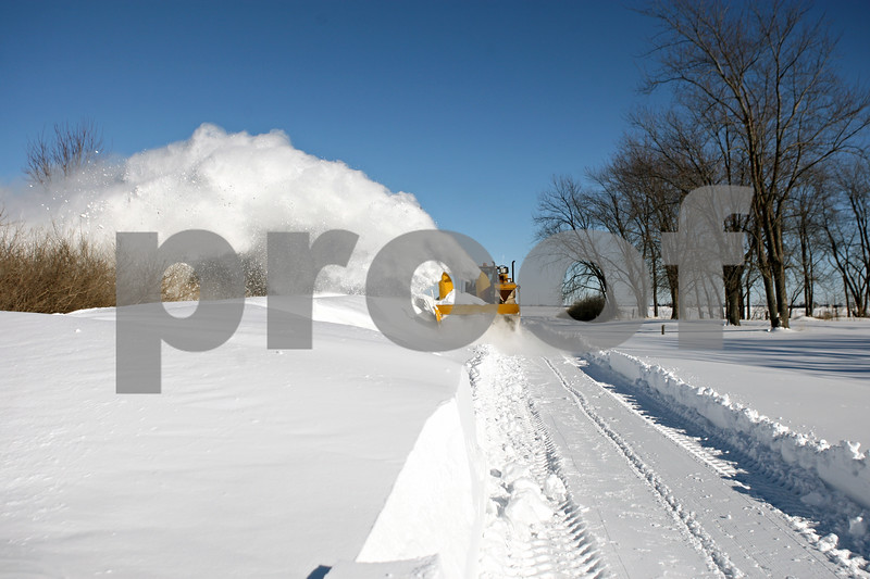 Rob Winner – rwinner@daily-chronicle.com<br /> <br /> A Clinton Township worker clears Lee Road just west of Route 23 near Waterman on Thursday afternoon.