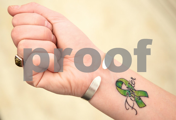 Kyle Bursaw – kbursaw@shawmedia.com<br /> <br /> Amberley Kowalski shows her wrist tattoo with a lime green cancer ribbon, the color representing Lymphoma. Kowalski said she was originally thinking of having her ink, which she received in late October, read 'Survivor' but decided on 'Fighter' because she is always going into battle with her Non-Hodgkin's Lymphoma.<br /> <br /> Taken at the Kishwaukee Hospital Cancer Center on Tuesday, Nov. 1, 2011.