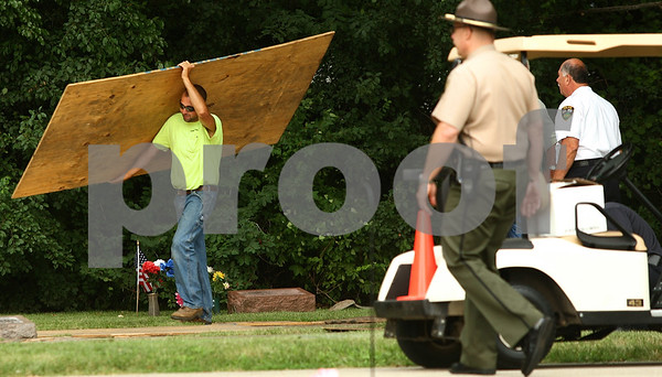 Kyle Bursaw – kbursaw@daily-chronicle.com<br /> <br /> After exhuming the grave of Maria Ridulph, Elmwood cemetery employee Lenny Reynolds Jr. removes boards and cleans up the area around the grave around 8:30 a.m. on Wednesday, July 27, 2011.