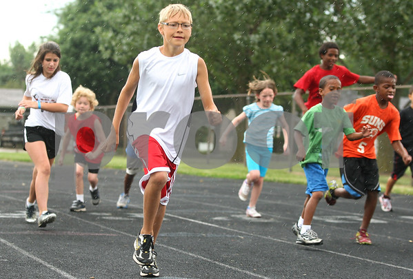 Kyle Bursaw – kbursaw@daily-chronicle.com<br /> <br /> Dylan Kvapil (center) does warm-ups with other members of the Huskie Track Club at the old DeKalb High School on Thursday, July 7, 2011. Ten-year-old Kvapil will attempt to qualify for the USATF national meet in the 1,500-meter run.