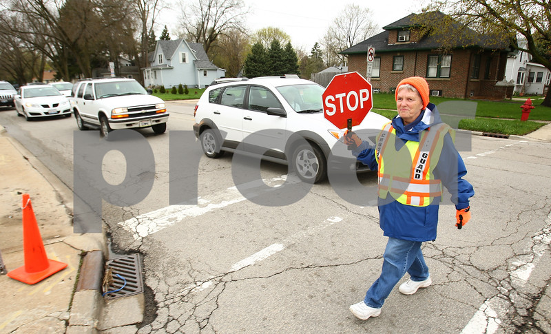 Kyle Bursaw – kbursaw@daily-chronicle.com<br /> <br /> Marlene Lave returns to the sidewalk after helping children cross Taylor street at the intersection of Fourth street in DeKalb, Ill. on Wednesday, April 27, 2011. Lave has been a crossing guard for seven years.