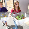 Kyle Bursaw – kbursaw@daily-chronicle.com<br /> <br /> Hannah Hanks (left) and Brooke Kron, both in EarlyACT at North Grove Elementary, load bins full of plants into vehicles outside their school on Tuesday, May 17, 2011. The plants were gifts to senior centers around the area.