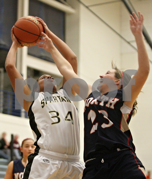 Rob Winner – rwinner@shawmedia.com<br /> <br /> Sycamore's Olyvia Rand (34) controls an offensive rebound over Belvidere North guard Autumn Neuhring (23) during the first quarter of the Central High School Thanksgiving Tournament championship game in Burlington on Wednesday, Nov. 23, 2011.
