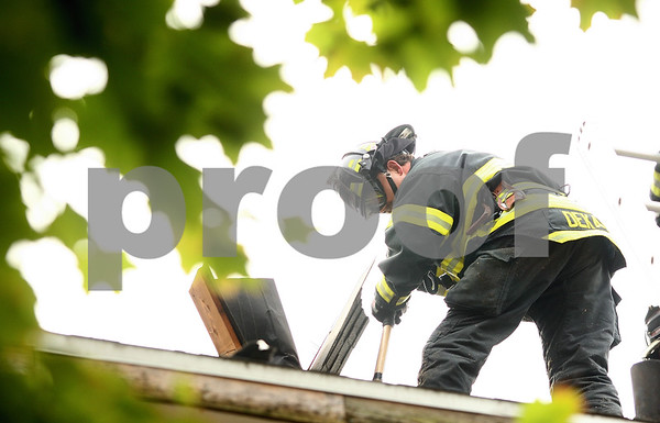 Kyle Bursaw – kbursaw@shawmedia.com<br /> <br /> Firefighter Adam Karolus uses an axe to break ventilation into the roof of a building on Oak Street that the DeKalb Fire Department was using for training on Tuesday, Oct. 18, 2011.