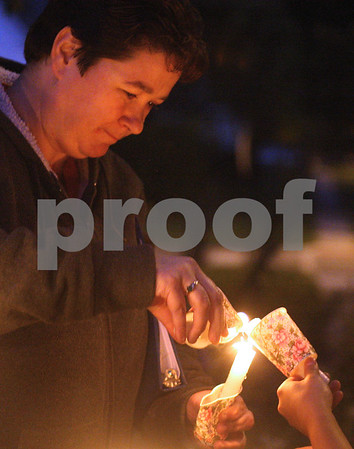 Kyle Bursaw – kbursaw@shawmedia.com<br /> <br /> Dawn Svoboda uses one candle to light another before the candlelight walk following the Safe Passage Vigil at the DeKalb Area Women's Center on Monday, Oct. 3, 2011.