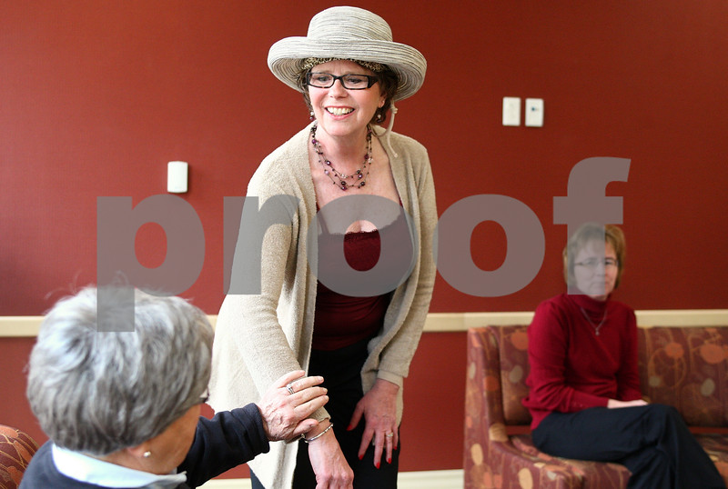 Kyle Bursaw – kbursaw@daily-chronicle.com<br /> <br /> Jane McDougall allows an attendee of a fashion show at the Kishwaukee Cancer Center to feel the soft material of a garment she models from Lehan Drugs.