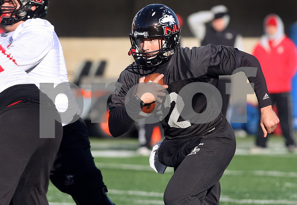 Kyle Bursaw – kbursaw@daily-chronicle.com<br /> <br /> Quarterback Chandler Harnish breaks out of the pocket at practice at Huskie Stadium on Thursday, March 24, 2011.