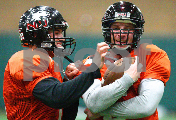 Kyle Bursaw – kbursaw@shawmedia.com<br /> <br /> Northern Illinois quarterback Chandler Harnish tries to strip the ball from fellow quarterback Jordan Lynch (right) while running a drill during practice at the DeKalb Recreation Center on Wednesday, Dec. 14, 2011.