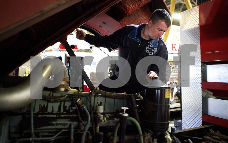 Kyle Bursaw – kbursaw@shawmedia.com<br /> <br /> During a routine maintenance check, DeKalb Firefighter Jim Ruhl checks fluid levels on a ten-year-old fire truck at DeKalb Fire Station no. 1 on Monday, Oct. 31, 2011.