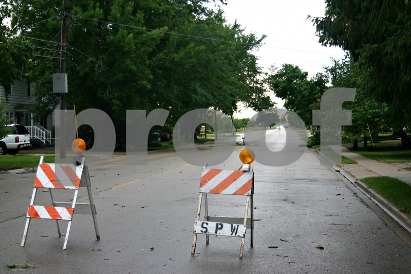 Barricades on Somonauk Street in Sycamore block off an area of the street where a power line hovers over the road Monday. The thunderstorm that moved through Monday morning left thousands in the area without power.<br /> <br /> Caitlin Mullen - cmullen@daily-chronicle.com