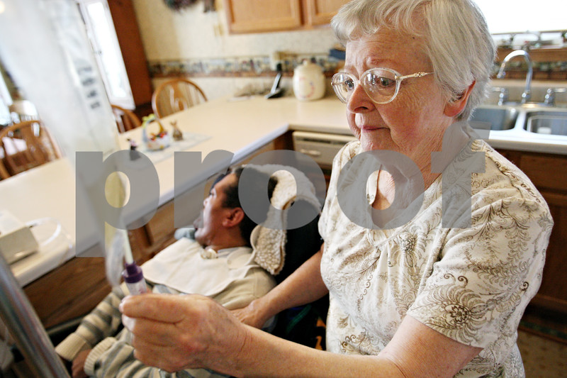 Rob Winner – rwinner@daily-chronicle.com<br /> <br /> Eileen Bosshart, 78, watches the flow of an antibiotic while caring for John Shepherd, 44, in the kitchen at Bosshart's home in Genoa, Ill. on Wednesday, May 4, 2011. Bosshart has been caring for Shepherd for 26 years.