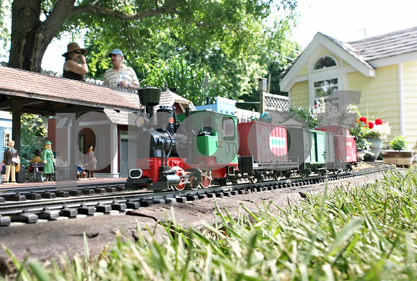 Rob Winner – rwinner@daily-chronicle.com<br /> <br /> A G scale train passes a model station in the backyard of Bill Riddle (right) as visitors came to see his garden on Saturday afternoon in Sycamore. Riddle's home was one of eight gardens featured during a garden walk presented by the University of Illinois Extension Master Gardeners.