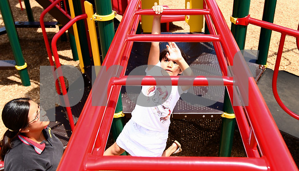 Kyle Bursaw – kbursaw@daily-chronicle.com<br /> <br /> Alexus Morrow, 5, tries to cross the monkey bars while her mother Maria Morrow looks on at Founders Elementary on Thursday, July 14, 2011.