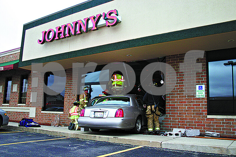 By ANDREW MITCHELL –amitchell@shawmedia.com<br /> Sycamore firefighters work to free an elderly woman trapped in her car after crashing through a window at the restaurant, Johnny's Charhouse Thursday. No injuries were reported.