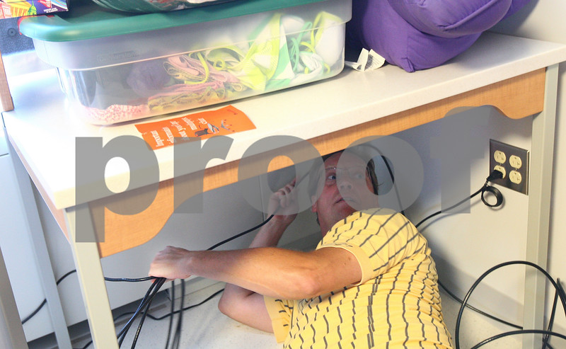 Kyle Bursaw – kbursaw@daily-chronicle.com<br /> <br /> Jeff Schmidt runs a wire underneath his daughter Liz's desk while setting up her new dorm room in Grant Tower C, the newly remodeled tower of Grant Hall on Thursday, Aug. 18, 2011.