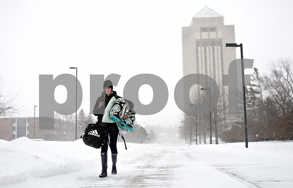 Rob Winner – rwinner@daily-chronicle.com<br /> <br /> Northern Illinois University student Christine Anderson carries an overnight bag, blanket and pillow while walking to a friends home in DeKalb on Tuesday afternoon. Anderson, who lives in Sandwich, thought it would be better to stay in town rather than travel home.