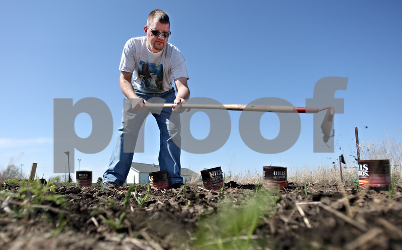 """Rob Winner – rwinner@daily-chronicle.com<br /> <br /> DeKalb resident Adam Brake uses a hoe to cultivate his rented garden plot  located on West Dresser Road in DeKalb on Friday, April 29, 2011. This is the second year that Brake has participated in the program. """"I have a strong history in gardening,"""" said Brake."""