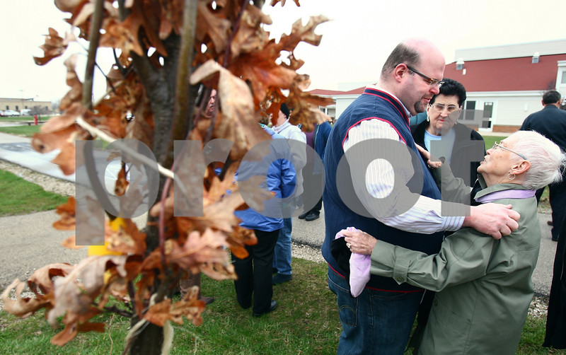 Kyle Bursaw – kbursaw@daily-chronicle.com<br /> <br /> Cory LaVigne hugs and speaks with attendees of his mother's dedication ceremony on Friday, April 22, 2011. A white oak tree (left) will be planted to remember Pat LaVigne at the DeKalb Nursing Home Grounds.