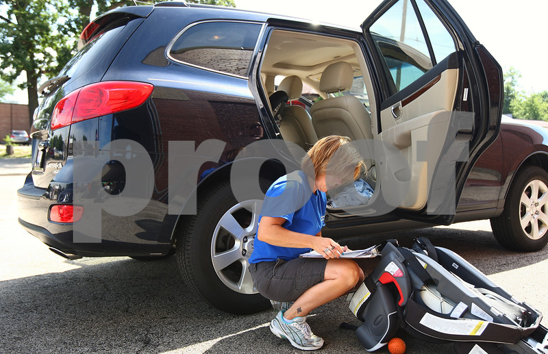 Kyle Bursaw – kbursaw@daily-chronicle.com<br /> <br /> Melanie Wingo, an Illinois Department of Transportation traffic safety liaison, looks at the bottom of a car seat in the parking lot of Jewel in DeKalb, Ill. on Friday, July 15, 2011.