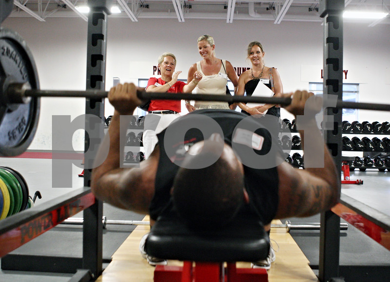 Rob Winner – rwinner@daily-chronicle.com<br /> <br /> Northern Illinois defensive end Sean Progar (front) lifts weights as Lyn Rasmussen (from left to right), of Chicago, Elisa Rubeck, of Sycamore, and Molly Green, of DeKalb, watch while participating in the third annual Football 101 Women's Clinic at the Yordon Center in DeKalb on Wednesday night.
