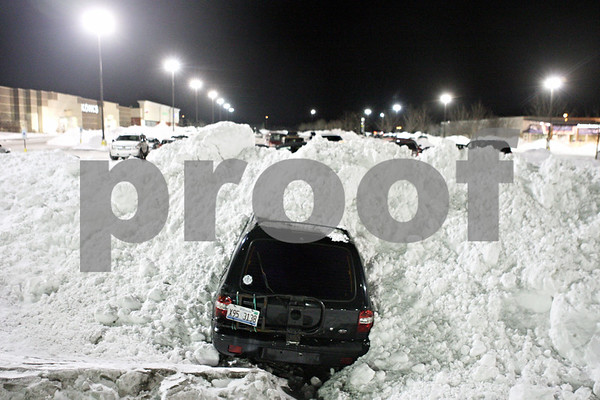 Rob Winner – rwinner@daily-chronicle.com<br /> <br /> A sports utility vehicle is plowed in at the parking lot near Best Buy as seen on Thursday evening in DeKalb.