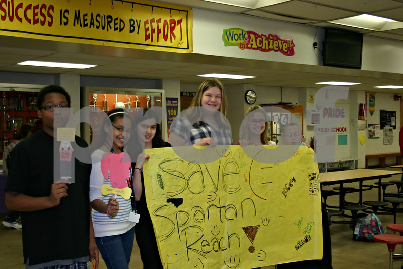 Students involved with Sycamore Middle School's Spartan REACH program show Wednesday the banner and stick figures they made to send to Gov. Pat Quinn, urging him to continue funding for the after-school and summer program. The program is largely funded through a $140,000 state grant that is not included in next year's budget.<br /> <br /> Caitlin Mullen - cmullen@daily-chronicle.com