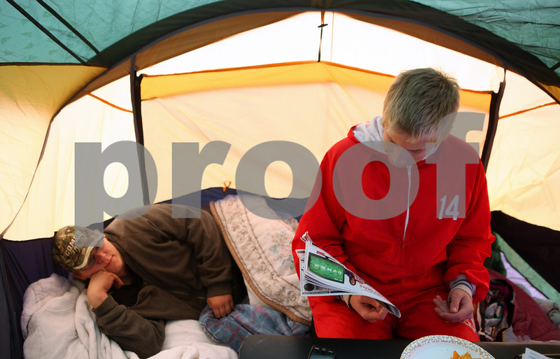 Kyle Bursaw – kbursaw@shawmedia.com<br /> <br /> Derrick Chmura, 17, looks over a Black Friday advertisement while his brother Bradley Chmura, 19, gets comfortable in the pile of pillows and blankets inside their tent in front of Best Buy on Thursday afternoon. The Chmura brothers and their mother Sherrie Taylor started waiting in line for Black Friday deals at 10:30 p.m. Wednesday.<br /> <br /> Thursday, Nov. 24, 2011.