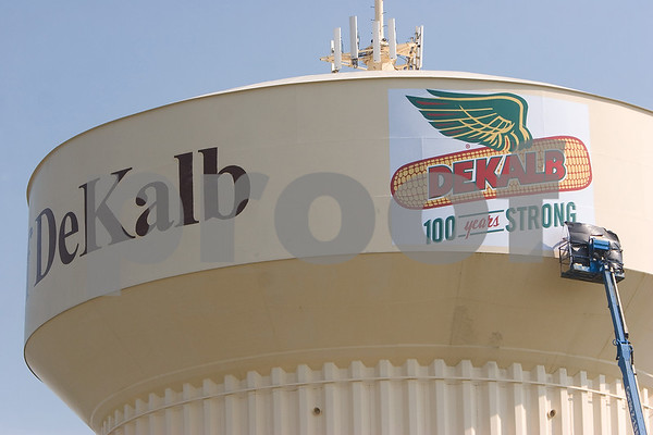Chronicle photo CURTIS CLEGG<br /> Workers from Billboards, Inc. from Dyer, Ind. adhere a vinyl sign commemorating the 100th anniversry of the DeKalb Seed Corn brand to the water tower on Dresser Road in DeKalb on Friday, September 2, 2011.