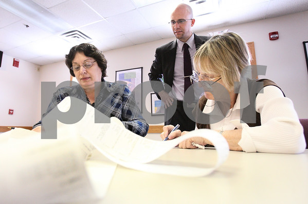 Kyle Bursaw – kbursaw@daily-chronicle.com<br /> <br /> Loretta Muller (left) and Mary Simons verify the counts of tests from the ballot counting machines while county clerk John Acardo looks on in Sycamore, Ill. on Wednesday, March 30, 2011 in preparation for the upcoming election. Muller was a representative from the Democratic party of DeKalb county, and Simons is from the Republican party of DeKalb county.