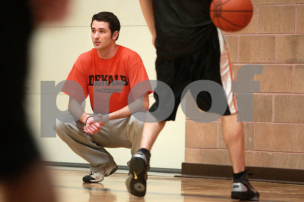 Kyle Bursaw – kbursaw@daily-chronicle.com<br /> <br /> Kyle Waller, a volunteer assistant on the DeKalb boys basketball team and 2006 graduate, looks on as the team does warm-ups during practice at DeKalb high school on Tuesday, Jan. 25, 2011.
