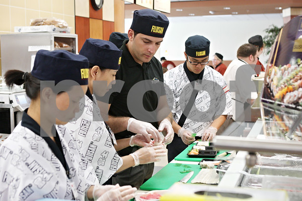 Rob Winner – rwinner@daily-chronicle.com<br /> <br /> Chef Ivan Dekic (third from left) helps train employees in making  sushi at the new Hy-Vee location in Sycamore on Monday afternoon.