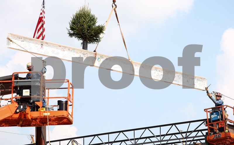 Kyle Bursaw – kbursaw@shawmedia.com<br /> <br /> Tom Tarner and Bob Untersee of Area Erectors position the final beam in the skeleton of the new student services building at Kishwaukee College on Friday, Aug. 19, 2011. As part of the topping off event, a small tree and a flag are attached to the top of the beam, which was also signed by Kishwaukee College students and staff.