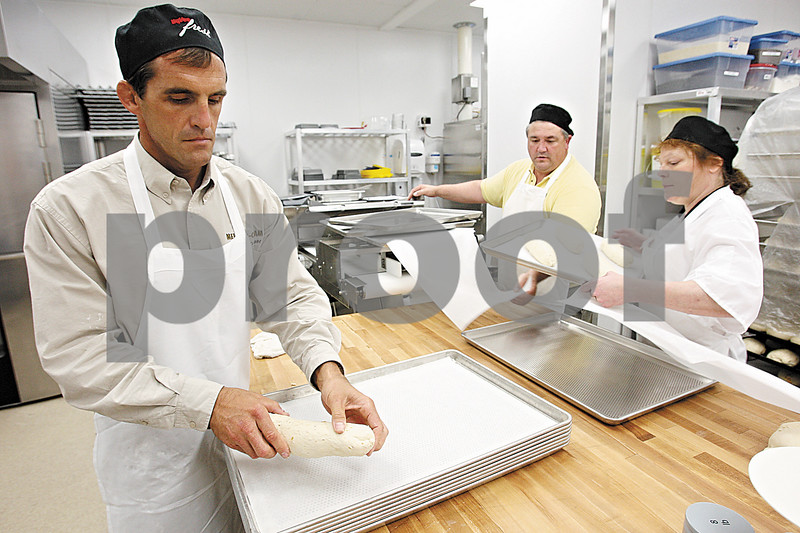 Rob Winner – rwinner@daily-chronicle.com<br /> <br /> Hy-Vee employees Pat Collins (from left to right), Den Morioni and Marie Hadley prepare loaves of bread in the bakery of the new Hy-Vee location on Monday afternoon in Sycamore.