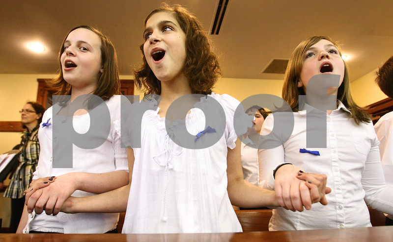 Kyle Bursaw – kbursaw@daily-chronicle.com<br /> <br /> Sycamore Middle School sixth grade students (from left) Merri Bork, Jenny Love and Emily Keiner sing and hold hands during Hands Around the Courthouse in one of the courtrooms at the DeKalb County Courthouse in Sycamore, Ill. on Thursday, April 28, 2011. Hands Around the Courthouse was relocated inside due to the weather.